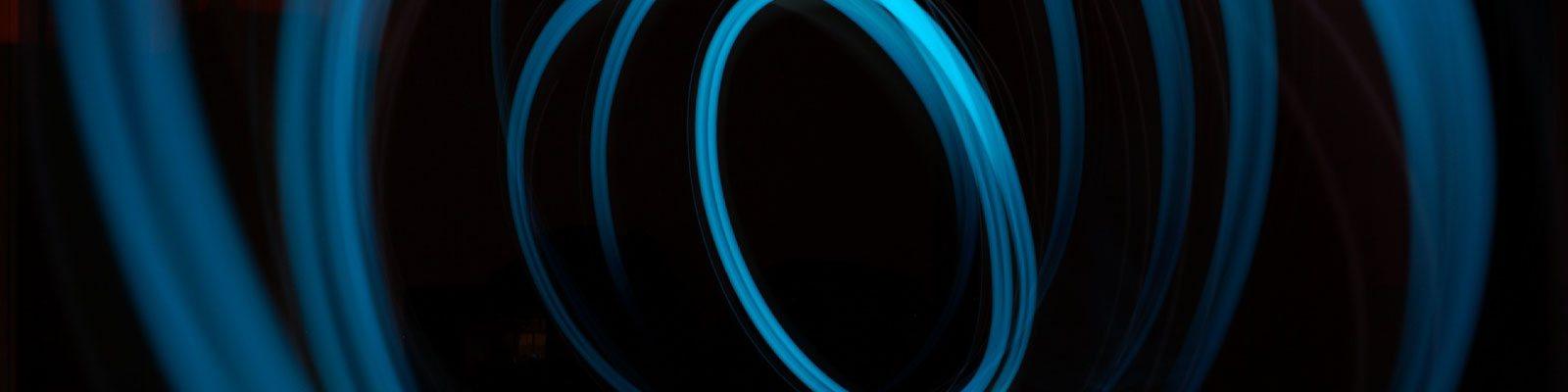 blue fiber optic strands swirling on black background
