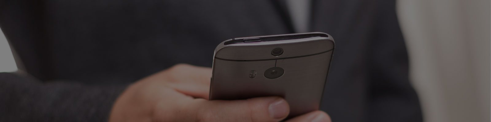 man using hosted pbx app on a grey smartphone