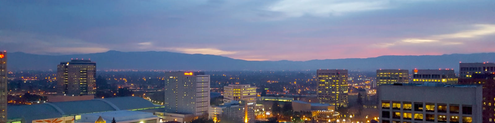 view of downtown San Jose CA at dusk, with lit buildings