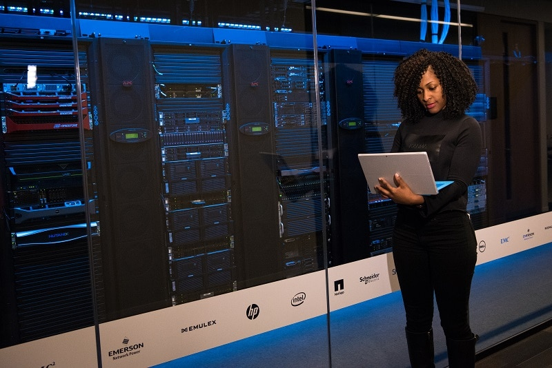woman standing with laptop in front of physical servers in hosting room