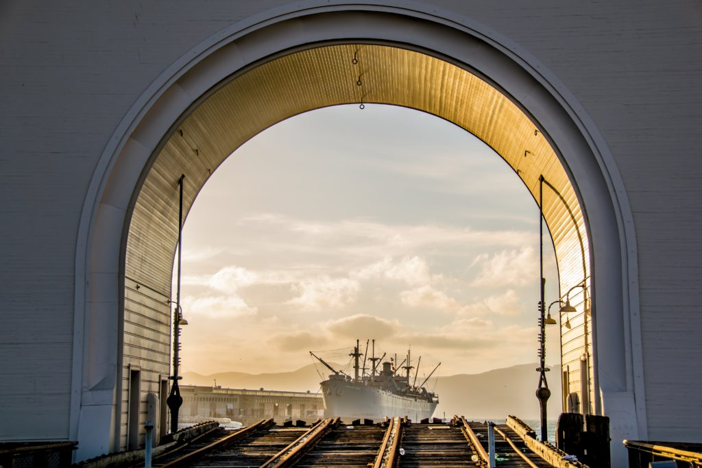 photo of ship on san francisco bay through arch structure