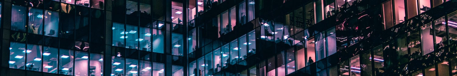 high rise office building with lights on at night