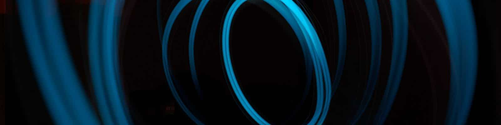 why is my internet slow blog post cover image - black with blue swirling fiber optics