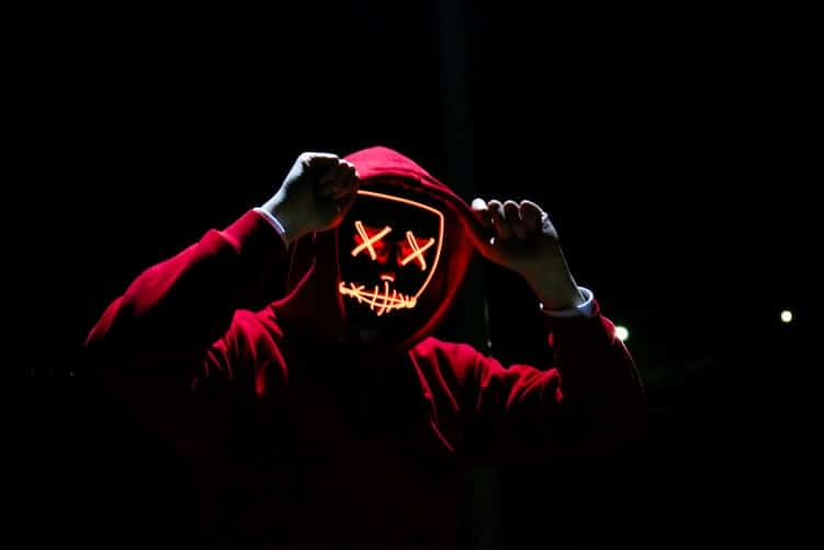 man wearing red hoody representing a hacker with neon light face mask