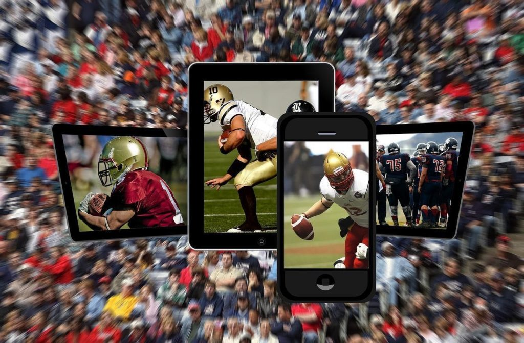 different mobile devices showing football players and matches with spectators blurred in the background