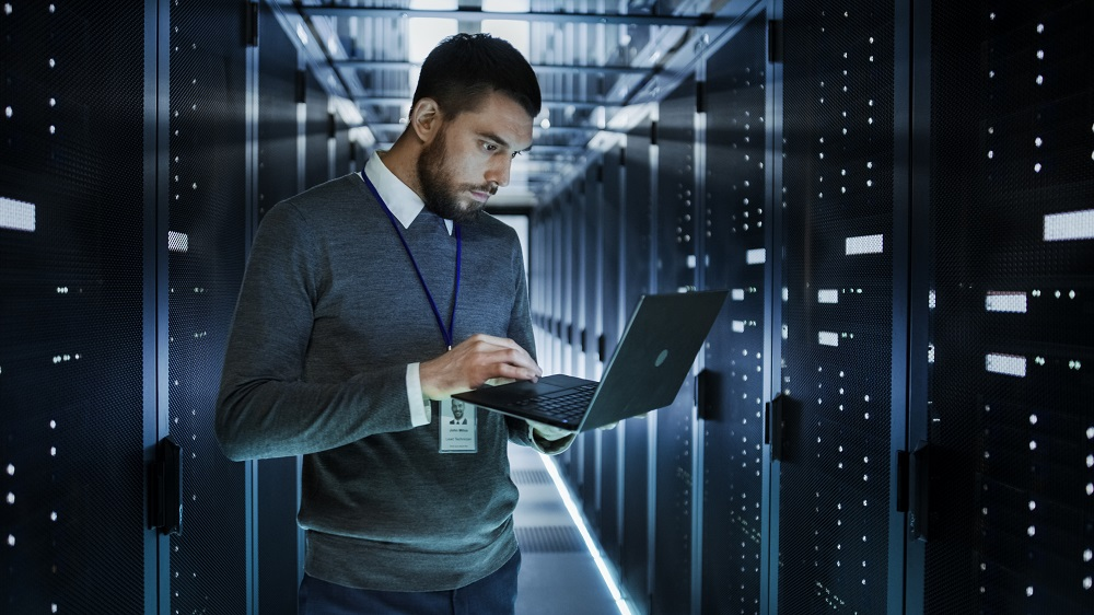 IT support technician checking laptop amongst servers in data center