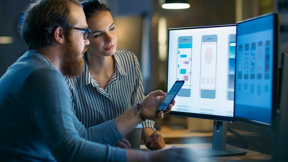 mobile app development - developers reviewing app designs on desktop and mobile device
