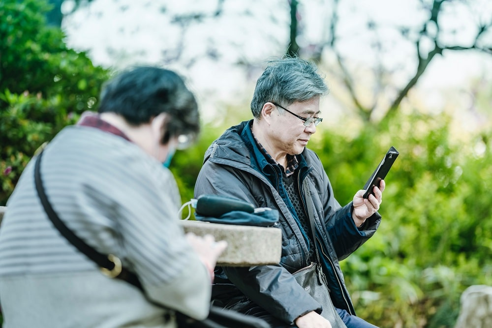 elderly asian couple using smartphones in the park