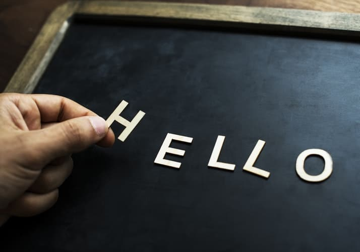 hello in white letters being added to a blackboard